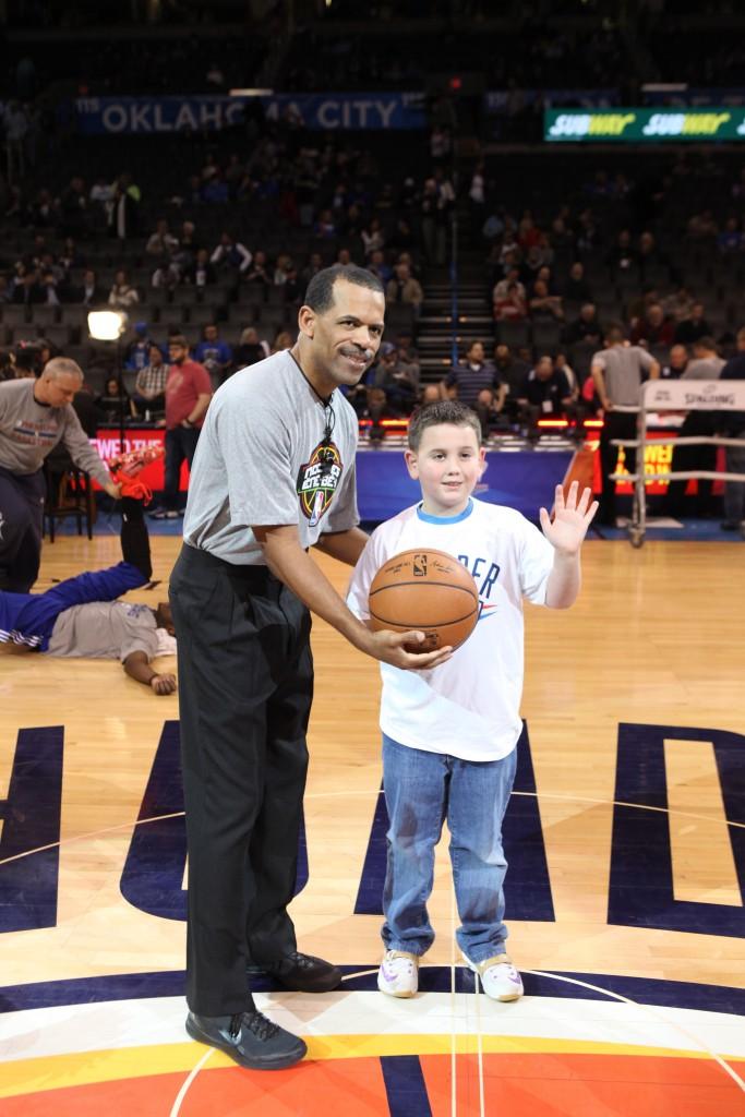 little boy shooting basketball at Thunder game